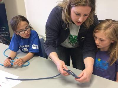Volunteer showing 2 young girls how to tie a knot.